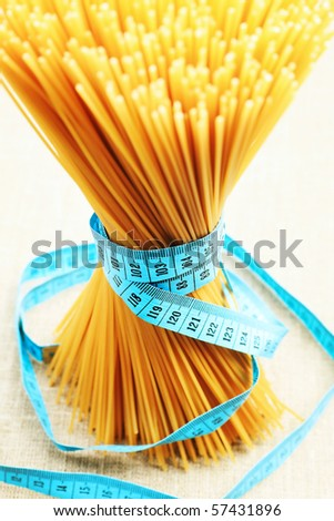 Food concept: bunch of uncooked spaghetti tied with tape measure.