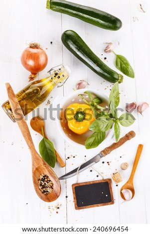 Food concept:  green and yellow organic vegetables, aromatic oil, herbs and spices over white wooden background. Top view - stock photo