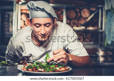 Food concept. Preparing traditional italian pizza. Young smiling chef in white uniform and gray hat decorate ready dish with green rucola herbs in interior of modern restaurant kitchen. Ready to eat.