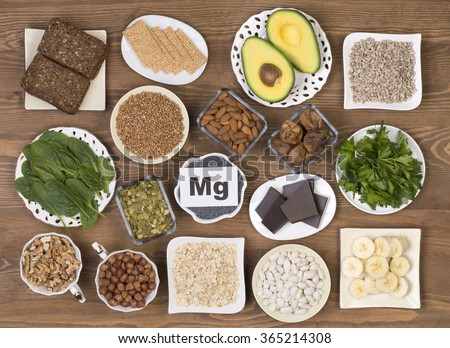 Food containing magnesium: pumpkin seeds, poppy seed, beans, chocolate, almonds, sunflower seeds, oatmeal, buckwheat, hazelnuts, sesame bars, figs,  spinach, bananas and avocado. - stock photo