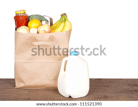 Food contents of a brown paper shopping bag on white - stock photo