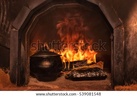 Food cooked in cauldron in Russian stove on fire
