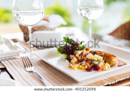 food, cooking and eating concept - close up of meat dish with garnish and water glasses on table at restaurant or home - stock photo