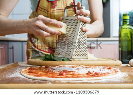 food cooking, culinary and people concept - cook or baker hands adding grated cheese to pizza at pizzeria