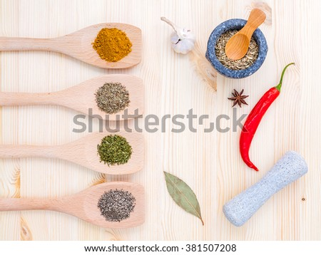Food Cooking ingredients. Dried Spices herb bay leaves,turmeric,chili,black pepper,fennel,star anise ,garlic ,thyme and oregano with the mortar on rustic wooden background. - stock photo