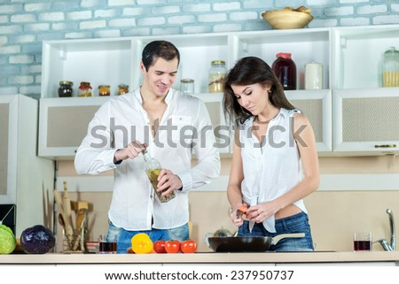 Food cooking together. Young smiling loving couple cook dinner or breakfast in kitchen while cut vegetables and drink cherry juice and watch the recipe of meal  on the tablet in apartment