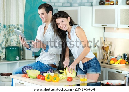 Food cooking together. Young smiling loving couple cook dinner or breakfast in kitchen while cut vegetables and drink orange juice and watch the recipe of meal  on the tablet in apartment - stock photo