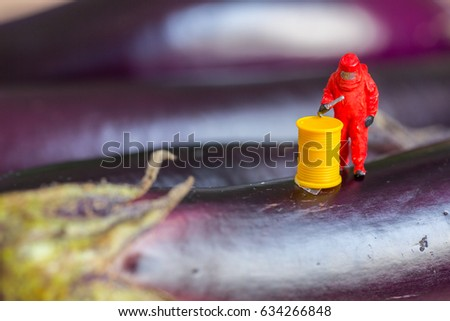 Food danger concept with farmer in protective suit and chemical pesticide orfertilizer drum on eggplant vegetable