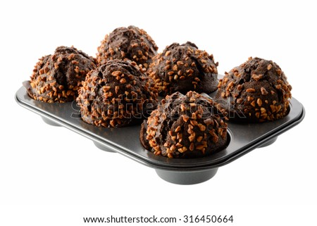 Food: dark chocolate muffins with roasted peanuts in baking pan, isolated on white background - stock photo