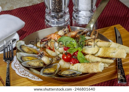 Food. Delicious roast with seafood: mussels, prawns, octopus, squid and vegetables at an expensive restaurant as a template for the menu background. Different points of focus and perspective - stock photo