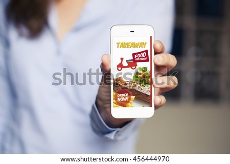 Food delivery take away app in a mobile phone screen. Phone in hand. - stock photo