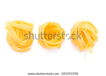 Food: dried italian pasta, fettuccine nests, isolated on white background - stock photo
