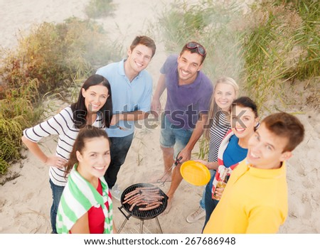 food, eating, cooking, summer holidays and people concept - group of friends having picnic and making barbecue on beach - stock photo