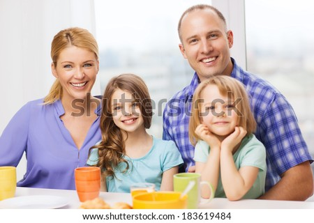 food, family, children, hapiness and people concept - happy family with two kids having breakfast at home - stock photo
