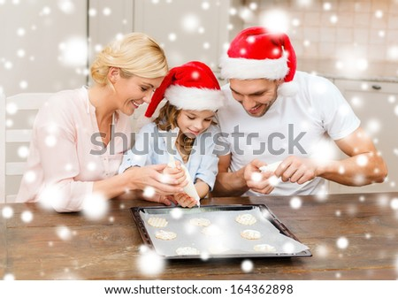 food, family, christmas, hapiness and people concept - smiling family in santa helper hats decorating cookies with glaze - stock photo
