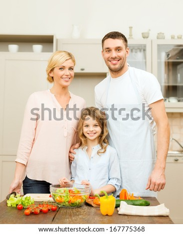 food, family, hapiness and people concept - happy family making dinner in kitchen - stock photo