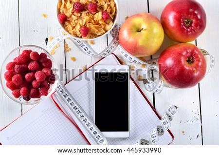Food for a healthy breakfast: cornflakes, fruit and berries in a plate, top view. Notebook, phone and tape measure for diet. - stock photo