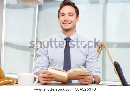 Food for thoughts. Pleasant smiling call center operator holding book and sitting at the table while reading. - stock photo