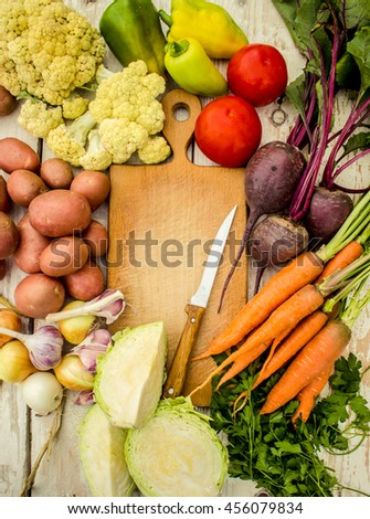 Food frame, market fresh food. Assorted organic vegetables and spices for healthy cooking and lifestyle on rustic wooden background with wooden cutting board in middle and copy space for text