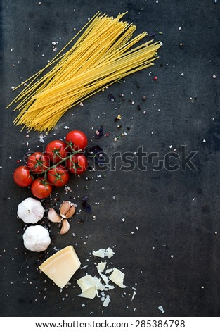 Food frame. Pasta ingredients. Cherry-tomatoes, spaghetti pasta, garlic, basil, parmesan and spices on dark grunge backdrop, copy space, top view - stock photo