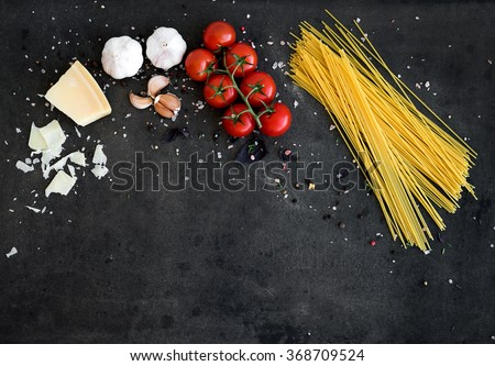 Food frame. Pasta ingredients. Cherry-tomatoes, spaghetti pasta, garlic, basil, parmesan and spices on dark grunge backdrop, copy space, top view, horizontal oriented - stock photo