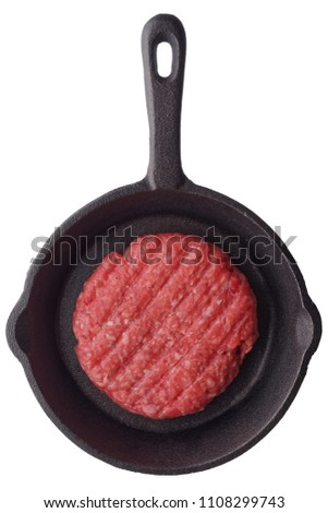 Food: fresh uncooked homemade burger on a frying pan, isolated on white background
