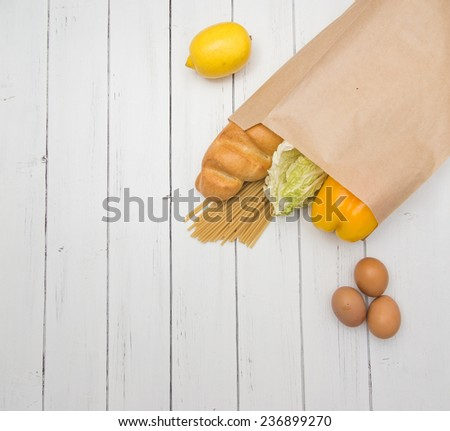 Food from supermarket in a paper craft bag on a white wooden background.  - stock photo