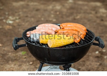 Food grill with corn sausage and cheese on brown dirt background - stock photo