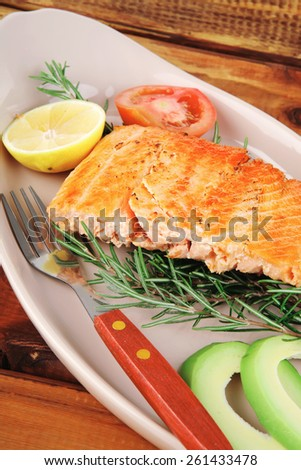 food: grilled salmon on big glass plate on wooden table - stock photo