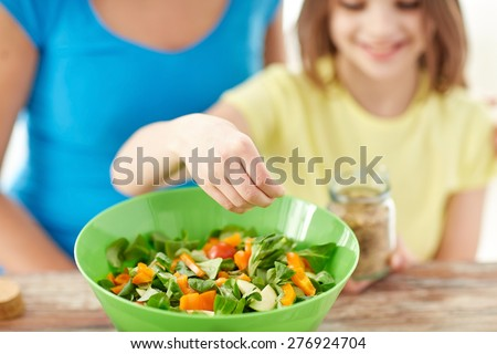 food, healthy eating, family and people concept - close up of happy girl and mother cooking salad for dinner and adding spices in kitchen - stock photo
