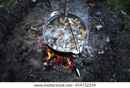 Food in a cauldron on a fire. Cooking outdoors in cast-iron cauldron.  - stock photo