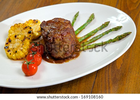 Food in the restaurant. Roasted meat with tomatoes, corn and asparagus