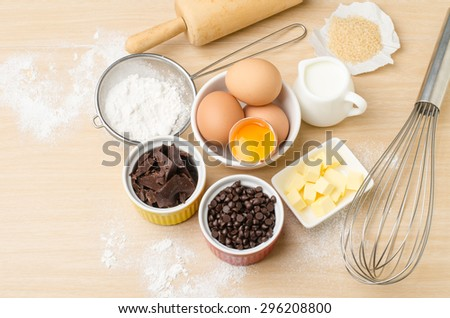 Food ingredient and recipe for backing (cake,dessert,sweet,chocolate),kitchen utensil and tool on wooden background - stock photo