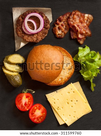 Food ingredients for burger constructing on black background. - stock photo