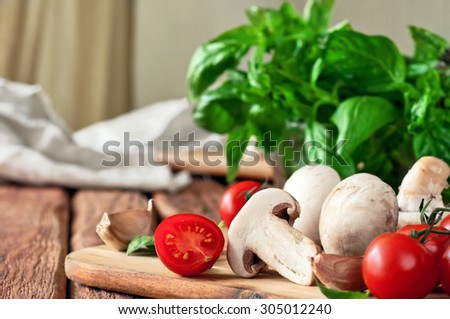 Food ingredients for pizza or pasta dishes. Fresh cherry tomatoes, mushrooms, garlic, basil leaves. Closeup. Copy space. Free space for text - stock photo