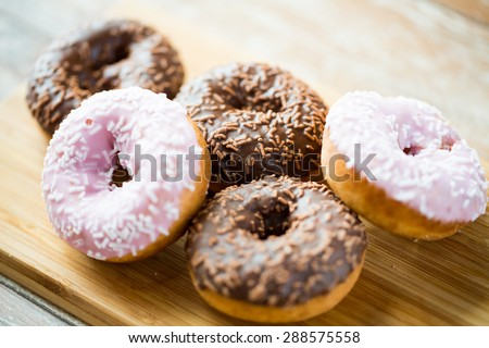 food, junk-food and eating concept - close up of glazed donuts on wooden board - stock photo