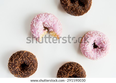 food, junk-food and eating concept - close up of glazed donuts over white - stock photo