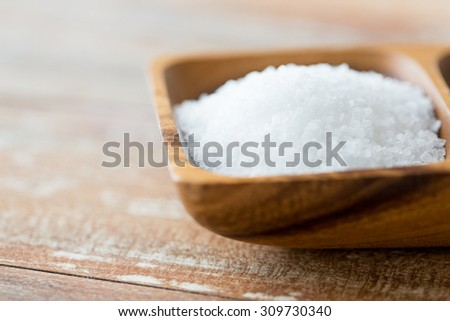food, junk-food, cooking and unhealthy eating concept - close up of white sea salt heap in wooden bowl - stock photo