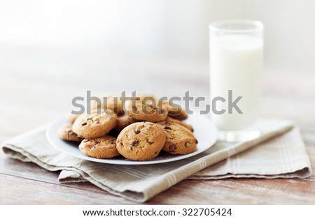 food, junk-food, culinary, baking and eating concept - close up of chocolate oatmeal cookies and milk glass on plate - stock photo