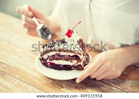 food, junk-food, culinary, baking and holidays concept - close up of woman eating chocolate cherry cake with spoon and sitting at wooden table - stock photo