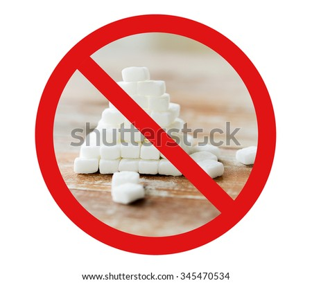 food, junk-food, diet and unhealthy eating concept - close up of white sugar pyramid on wooden table over red circle-backslash no sign - stock photo