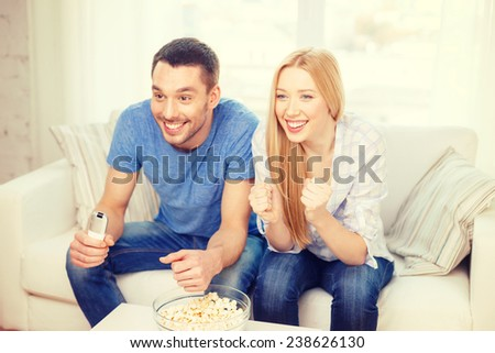 food, love, family, sports, entertainment and happiness concept - smiling couple with popcorn cheering sports team at home - stock photo