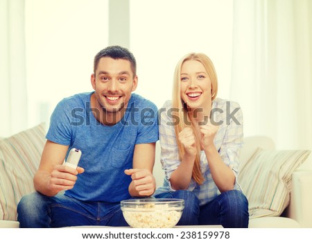 food, love, family, sports, entretainment and happiness concept - smiling couple with popcorn cheering sports team at home - stock photo