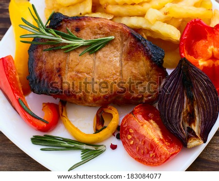 Food. Meat barbecue with vegetables on wooden surface. Meat steak. Beef steak bbq. Tomatoes, peppers, spices for cooking meat.
