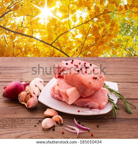 Food, meat, pork. Meat barbecue with spices on wooden surface. Meat steak. Beef steak bbq. Tomatoes, peppers, spices for cooking meat. Space for text menu diet recipe. Autumn landscape, background. - stock photo