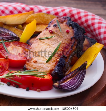 Food, meat, roast pork. Meat barbecue with vegetables on wooden surface. Meat steak. Beef steak bbq. Tomatoes, peppers, spices for cooking meat. - stock photo