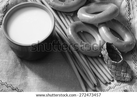 food milk in a glass straw bagels and pretzels on flax background
