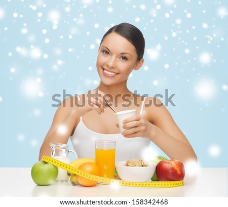 food, nutrition, slimming, diet concept - young woman with healthy breakfast and measuring tape - stock photo