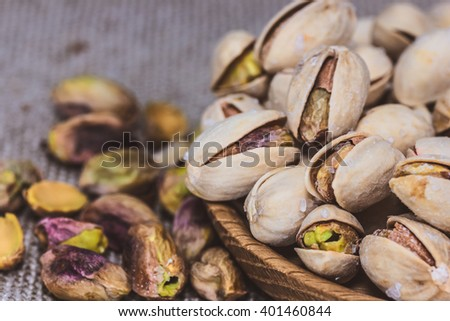 Food nuts pistachio in a wooden plate close up with shells and peeled healthy nutrition health organic food modern lifestyle selective focus and empty copy space