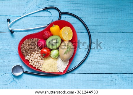 Food on heart plate with stethoscope cardiology concept on blue boards - stock photo